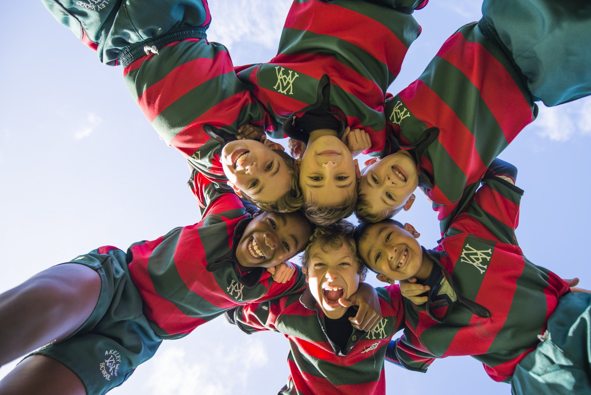 Boys from akeley wood school, looking down at the camera in a circle wearing their rugby shirts.